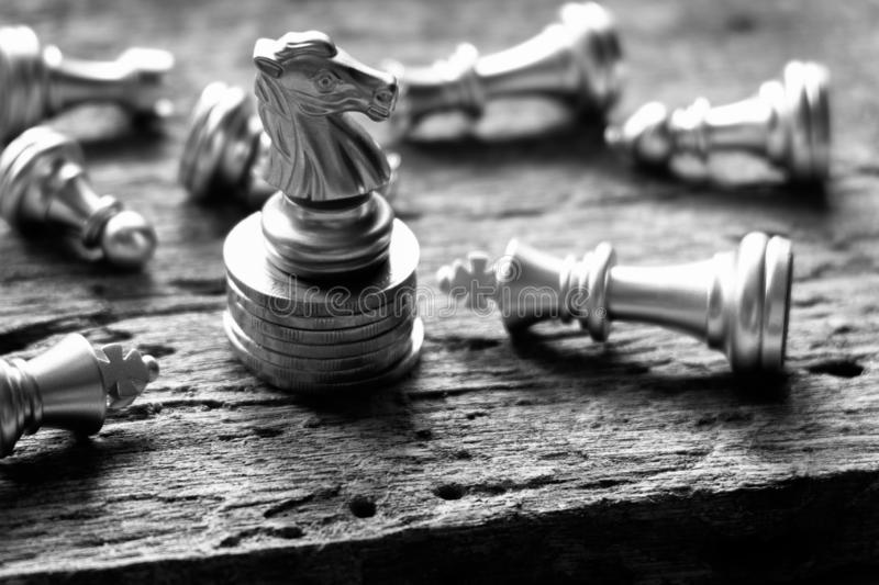 Last knight stand. The winner with advantage position, stand on top of coins refer to money is an principle asset for any business. Battle. Black&White. Copy stock photography