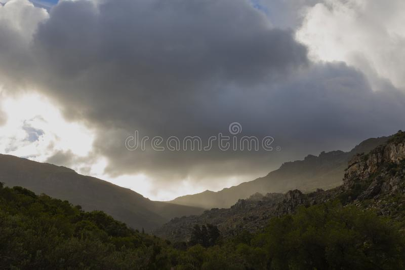 Last light of the day shine through a neck in the mountain. South Africa royalty free stock image