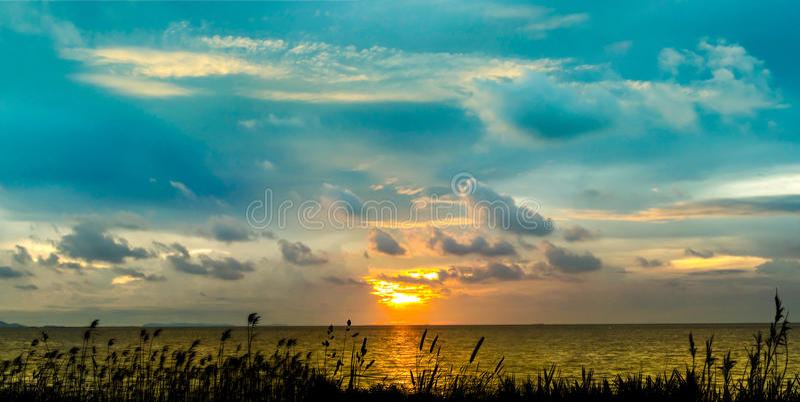 Last light of panorama sunset on horizon line over sea and glass. Last light of panorama sunset on horizon line over sea glass shadow in the evening twilight stock photo