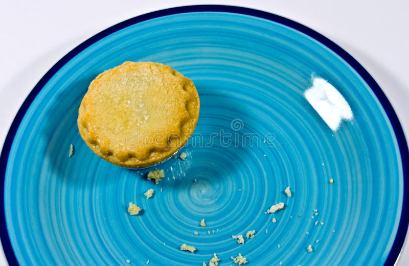 Last mince pie. A closeup of the last mince pie with a few crumbs on a pottery plate stock image