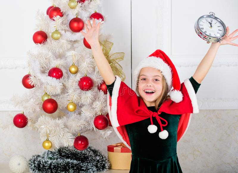 Last minute new years eve plans that are actually lot of fun. New year countdown. Girl kid santa hat costume with clock stock photo