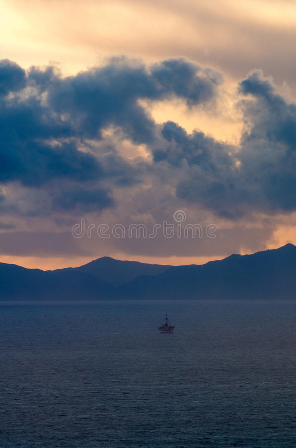 Last minutes of day. A lone beachgoer watches the end of the days sunset royalty free stock photo