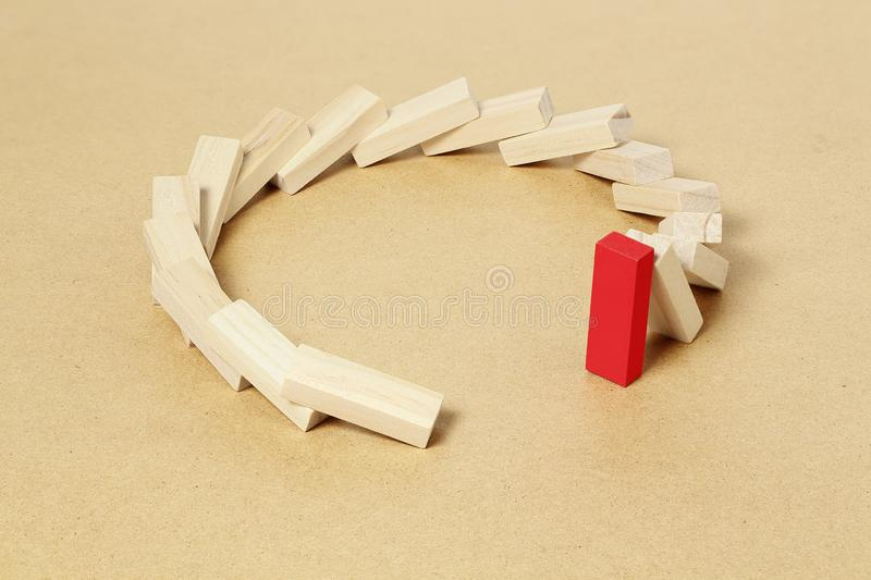 Last piece standing. Red toy block refusing to fall, abstract leadership or different concept royalty free stock photo