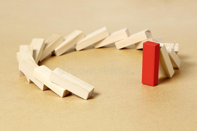 Last piece standing. Red toy block refusing to fall, abstract leadership or different concept stock photography
