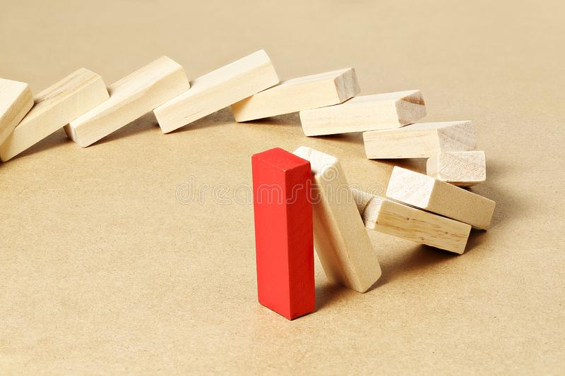 Last piece standing. Red toy block refusing to fall, abstract leadership or different concept stock image