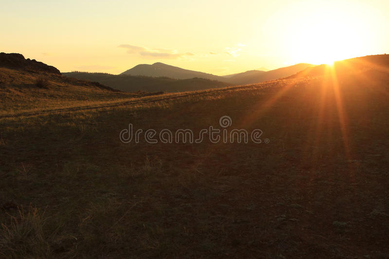 The last rays of the setting sun in the mountains royalty free stock photography