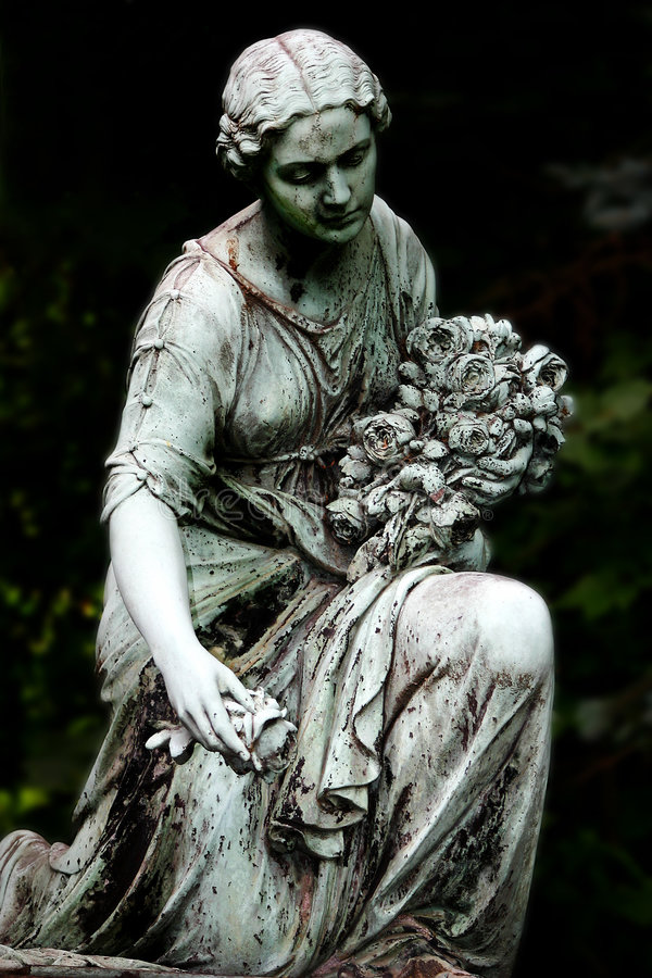 The Last Roses. Statue with roses at a cemetary in Leipzig/Germany royalty free stock images