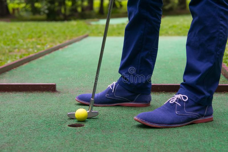 Last shot of the ball in the pocket, mini Golf club, close-up, men`s legs stock photos