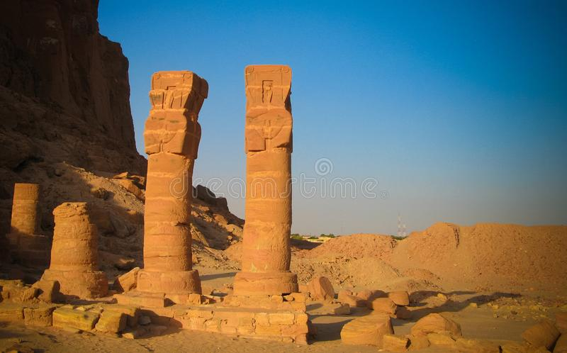 Last standing pillars of Napata`s temple of Amun at the foot of Jebel Barkal mountain at Karima, Sudan. Last standing pillars of Napata`s temple of Amun at the stock images