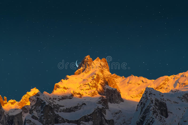 Last sun of the mountains. With the moon and the stars stock photo