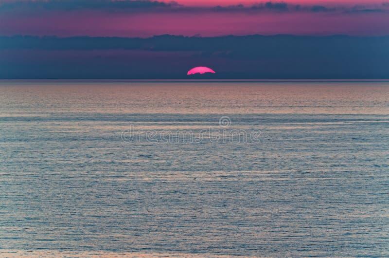 Last sun rays above tyrrhenian sea - sunset. Sun behind the horizont. View from Riaci beach near Tropea, Italy royalty free stock photos