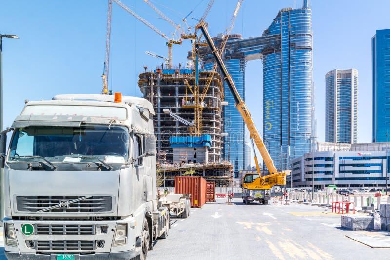 Lastbil och kranar i en konstruktionsplats - byggande skyskrapa under konstruktion royaltyfri fotografi