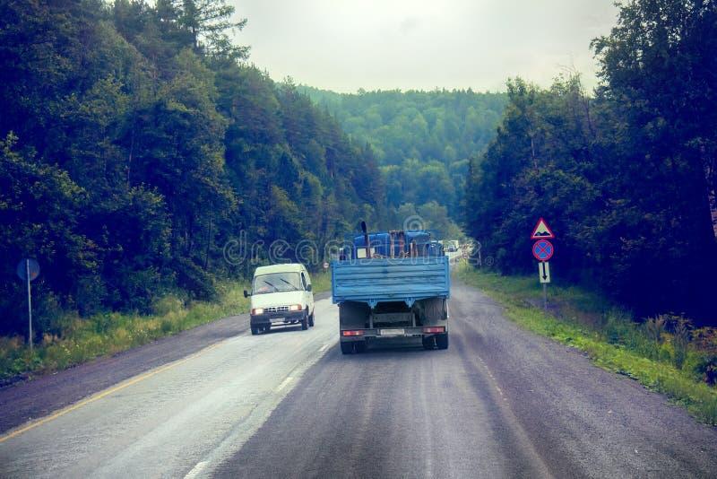 Lastbil på huvudväg-leverans av gods i dåligt väderhot foto från taxin av en stor lastbil överst arkivbild