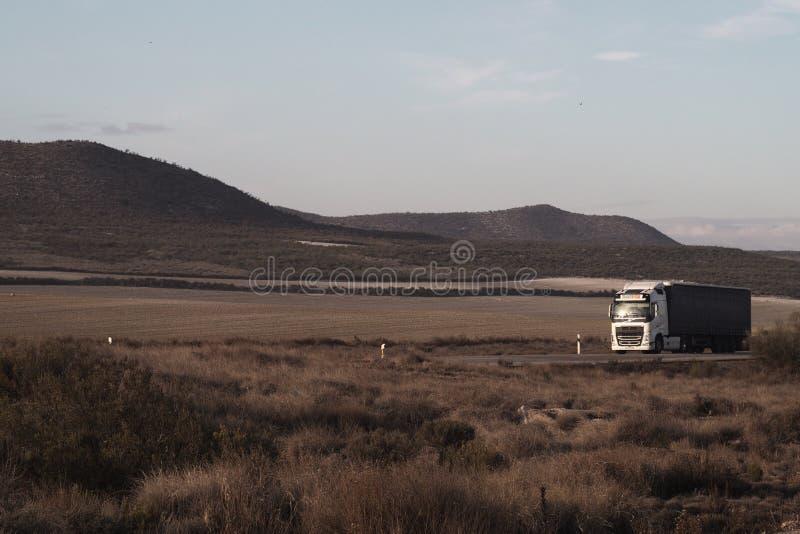 Lastbil på huvudvägen på öken arkivfoton