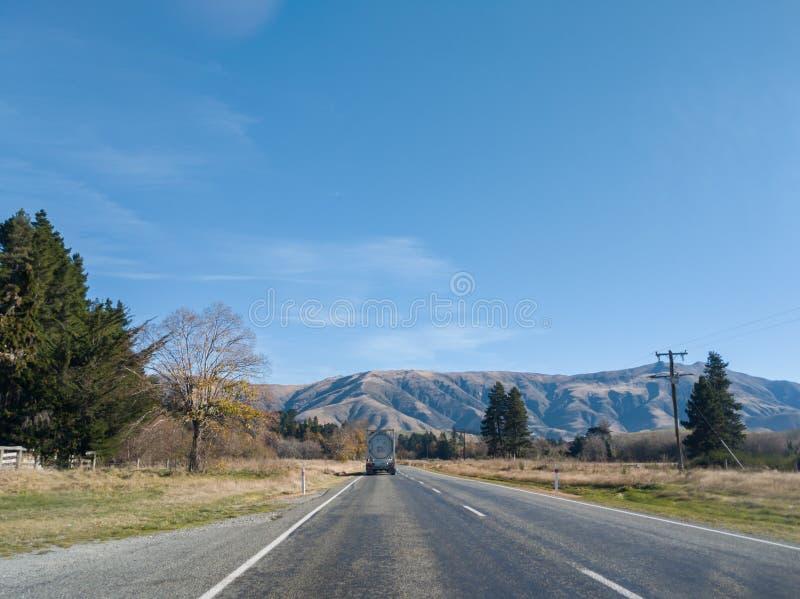 Lastbil på vägen i Nya Zeeland med sikt av berg i bakgrunden royaltyfria bilder