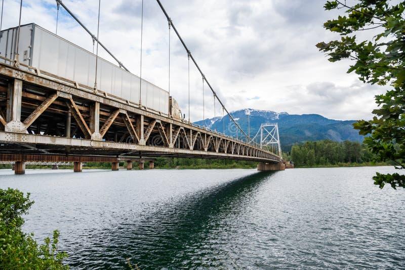Lastbil som korsar en Suspemsion bro över en flod i bergen arkivfoton