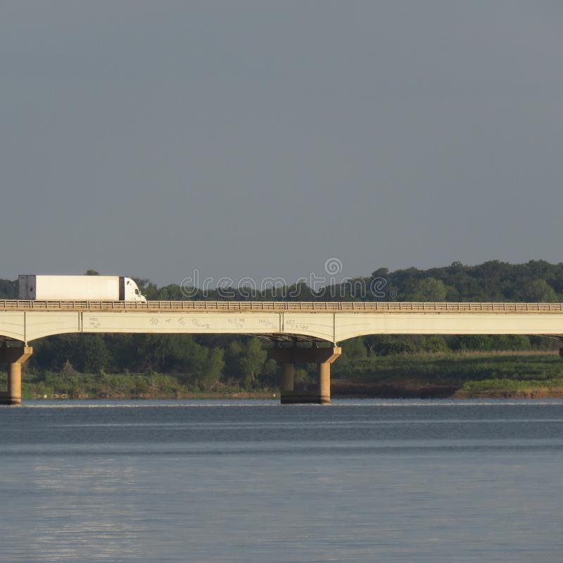 Lastbil som rusar ner USA-rutt 377 över den sjöTexoma Graffitied bron royaltyfria foton