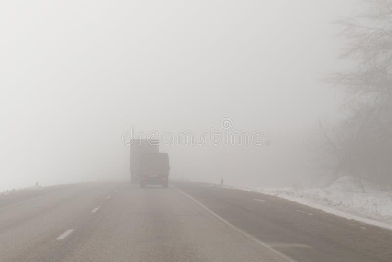 Lastbilar på en dimmig väg royaltyfri bild