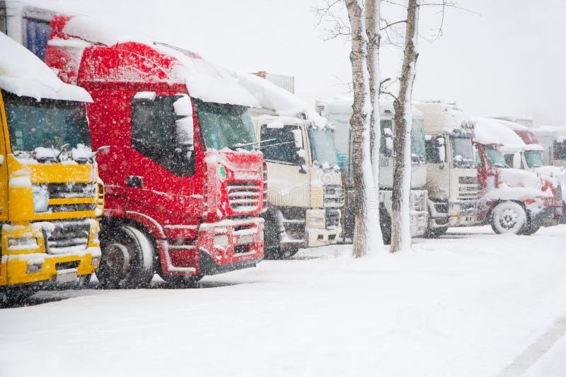Lastbilar som parkerar i sträng vinterstorm Förbud av trafik i tung snö royaltyfri bild