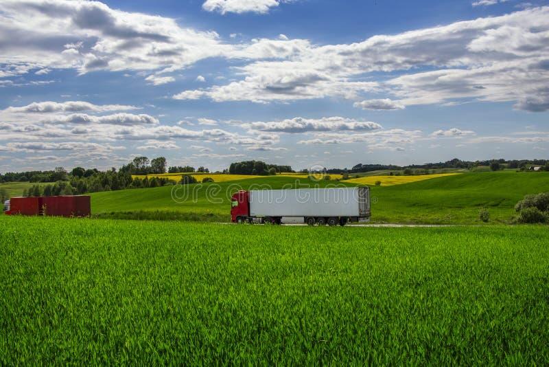 Lastbilar som transporterar gods på asfaltvägen mellan gräsplanfält i ett lantligt landskap under en molnig blå himmel arkivfoto