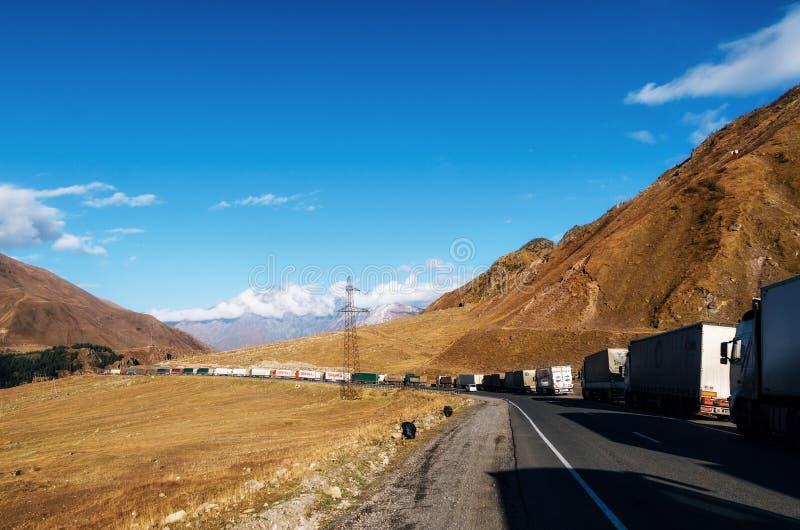 Lastbilar ställer upp i kö på den georgiska militära vägen arkivbilder