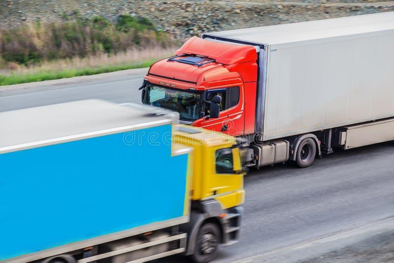 Lastbilar transporterar gods i motsatt riktning arkivbilder