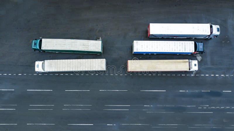 Lastbilar väntar på att lastas i logistikcentrets flygfotografering i toppvyn från en drone arkivfoto
