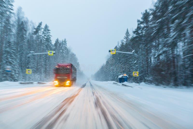 Lastbildrev med billyktor på vintervägen i en snöstorm i aftonen, då snö skulle flyga Begrepp av körning fotografering för bildbyråer