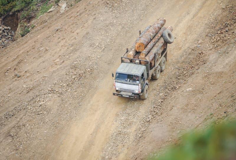 Lastbilen bär loggar in en grusväg arkivfoto
