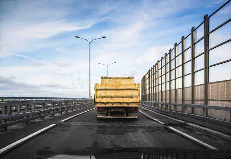 Lastbilen går på asfaltvägen, bakre sikt arkivfoton