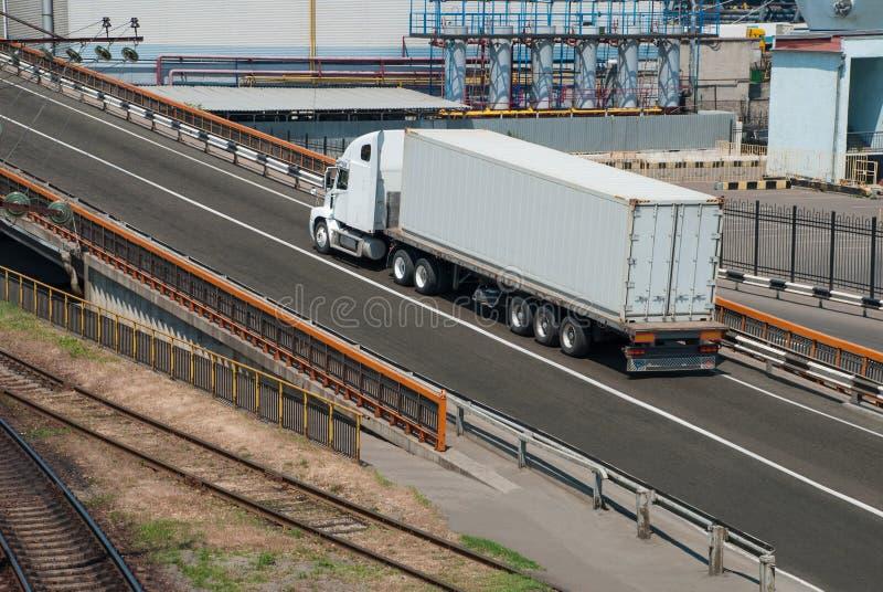 Lastbilen kör nära växten royaltyfri bild
