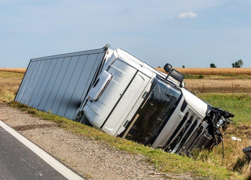 Lastbilen ligger i ett sidodike efter vägolyckan arkivbilder