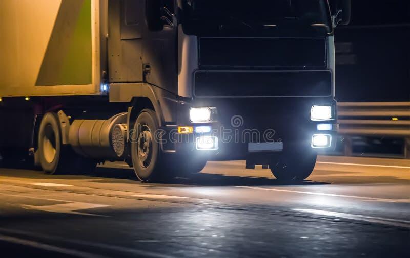 Lastbilflyttningar på huvudvägen på natten royaltyfri foto
