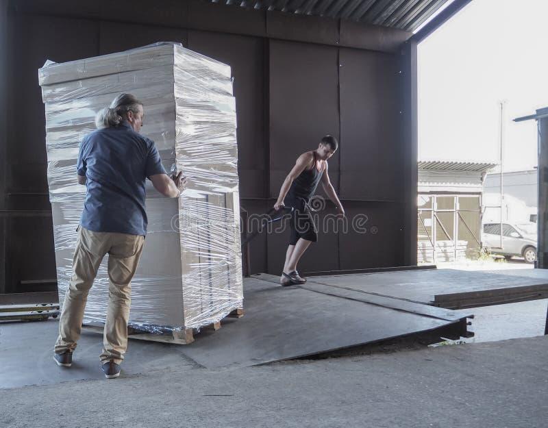 Lastbilpäfyllning och sändnings Manliga arbetare laddar godset i kartonger på en lastbil royaltyfria bilder