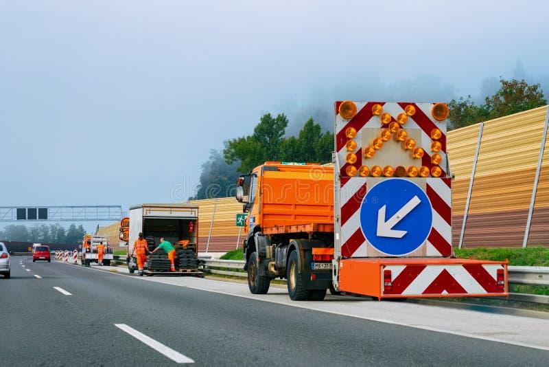 Lastbilpil ner vänstert reflekterande riktningsvägmärke royaltyfria bilder