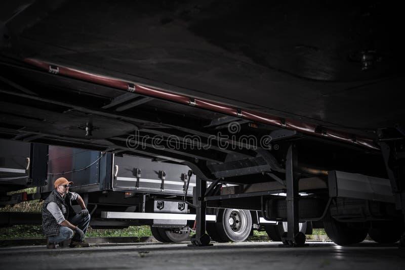 Lastbilsförare som kontrollerar släp arkivfoto