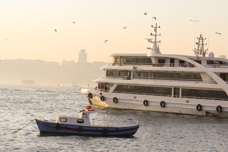 Lastfartyg med det lilla fartyget på solnedgångtid royaltyfri foto