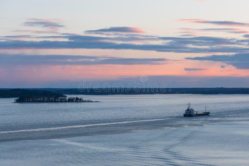 Lastfartyg på en djupfryst flod på solnedgången arkivfoton