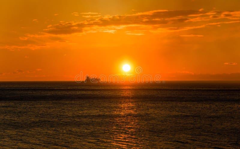 Lastfartyg på horisonten på solnedgången arkivbild