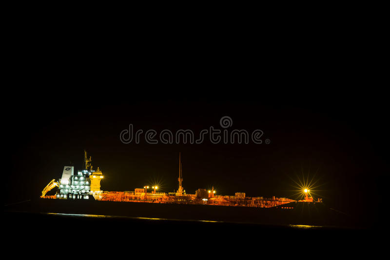Lastfartyg på natten arkivfoton