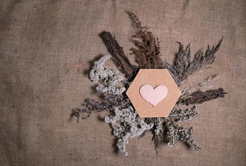 Lasting faded sustainable flowers with hexagonal frame and cardboard heart on natural canvas background. Composition of dried royalty free stock images