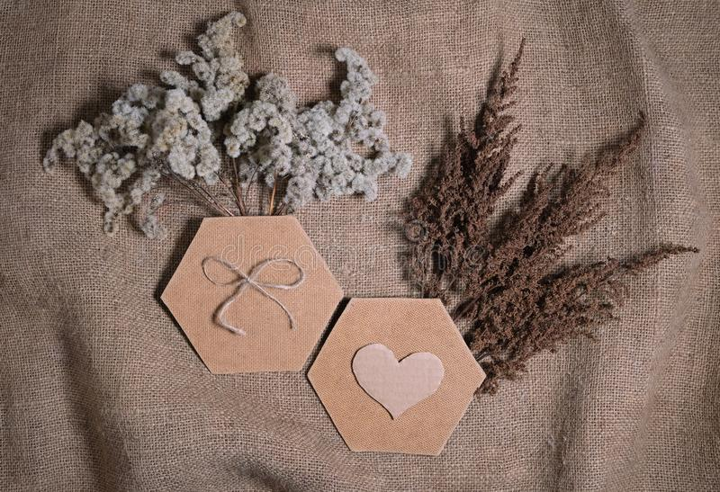Lasting faded sustainable flowers with two hexagonal frame and cardboard heart on natural canvas background. Composition of dried royalty free stock images