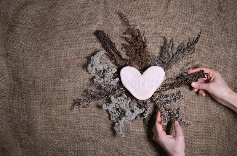 Lasting faded sustainable flowers with wooden heart on natural canvas background. Human hands making composition of dried flowers royalty free stock photos