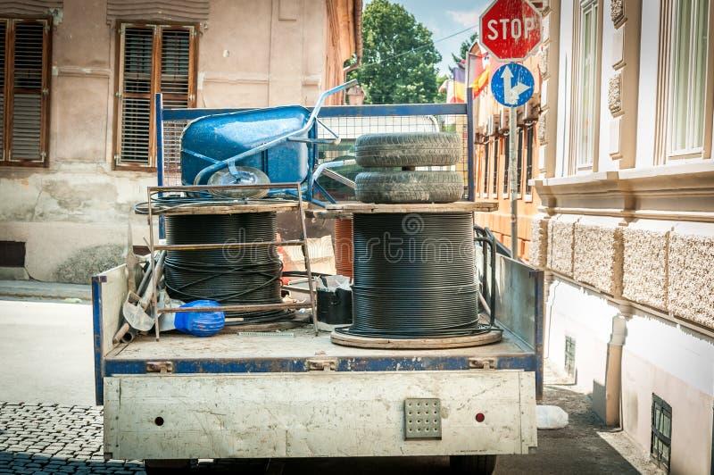 Lastlastbilen mycket av hjälpmedel och underjordiska optiska kablar rullar för den parkerade internet på gatan för rekonstruktion royaltyfri foto