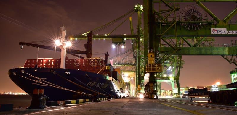Lastoperationer på den upptagna behållareterminalen under natt royaltyfria bilder