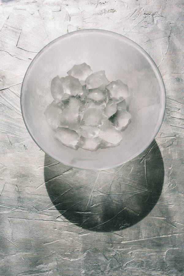 Lastra di vetro con ghiaccio Grandi cubetti di ghiaccio su un fondo strutturale grigio Ombra dura dal sole Luce del giorno natura fotografia stock