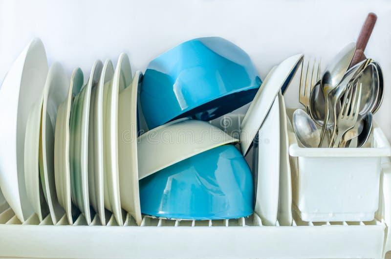 Lastre bianche e blu per l'alimentazione, forchette per posate, coltelli, cucchiai in un vetro per l'asciugatura di piatti in cuc fotografia stock libera da diritti