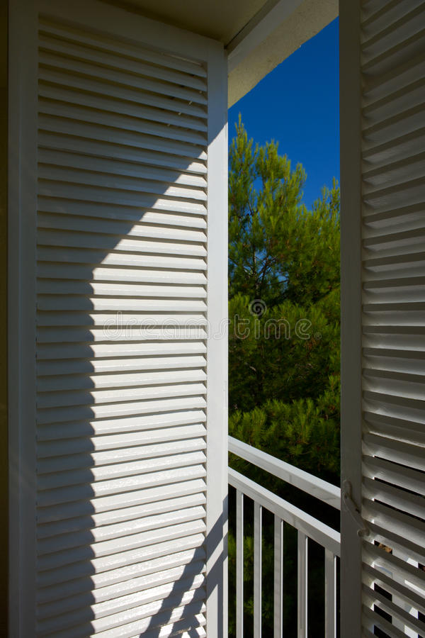Lasts shutters. Balcony with open louver shutters on a sunny day royalty free stock images