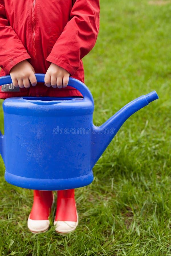 4 lat chłopiec w czerwonej kurtce gumowych butach i iść nawadniać drzewa od ładnej dużej błękitnej podlewanie puszki i zdjęcie stock