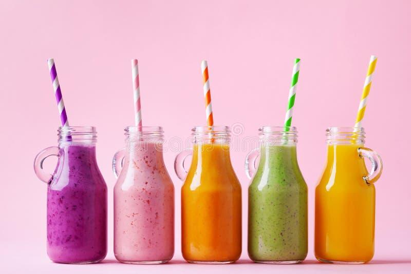 Lat kolorowi owocowi smoothies w słojach na różowym tle Zdrowy, detox i diety jedzenia pojęciu, zdjęcia royalty free